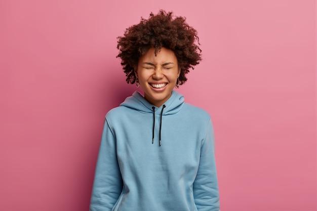 기뻐 곱슬 머리 여자의 초상화는 눈을 닫고 광범위하게 미소