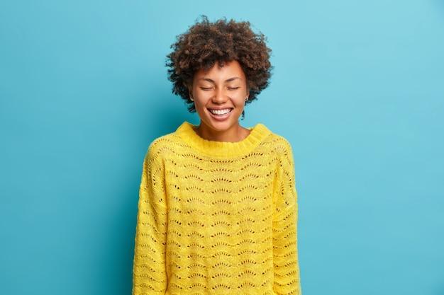 기뻐하는 부드러운 여자의 초상화는 광범위하게 눈을 감고 하얀 치아가 파란색 벽 위에 고립 된 긍정적 인 감정을 표현하는 캐주얼 노란색 니트 점퍼를 착용하는 것을 보여줍니다.