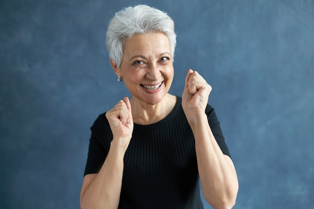 陽気な広い笑顔でカメラを見て、拳を握りしめ、興奮を表現するスタイリッシュなヘアカットで大喜びの幸せな女性年金受給者の肖像画。