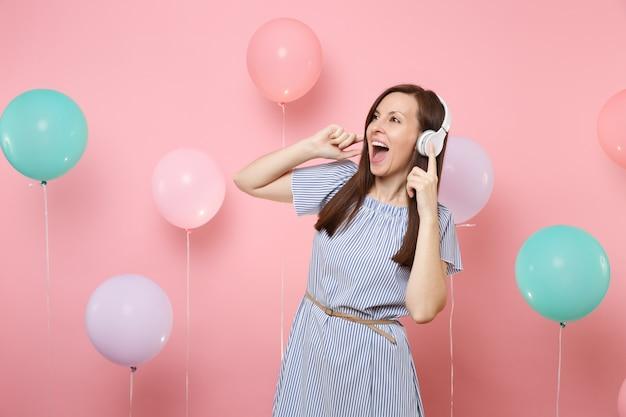 カラフルな気球とパステルピンクの背景に音楽を聞いて青いドレスを着てヘッドフォンで大喜びの幸せな若い女性の肖像画。誕生日の休日のパーティーの人々の誠実な感情の概念。