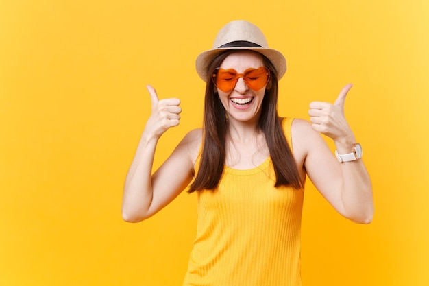 Портрет обрадованной смеющейся молодой женщины в соломенной летней шляпе, оранжевых очках, показывая большие пальцы руки вверх, копией пространства, изолированного на желтом фоне. люди искренние эмоции, концепция образа жизни. рекламная площадка