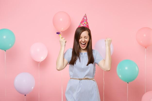 화려한 공기 풍선과 함께 분홍색 배경에 비명을 지르는 승자 제스처를 하는 생일 모자 파란색 드레스에 파티 휘파람과 함께 기뻐하는 여자의 초상화. 생일 휴가 파티, 사람들은 진심 어린 감정.