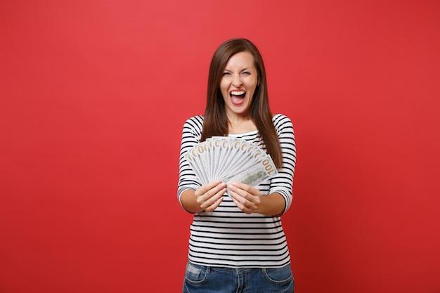 줄무늬 옷을 입은 기뻐하는 젊은 여성의 초상화는 붉은 벽 배경에 격리된 많은 달러 현금 돈을 들고 비명을 지르고 있습니다. 사람들은 진심 어린 감정 라이프 스타일 개념입니다. 복사 공간을 비웃습니다.