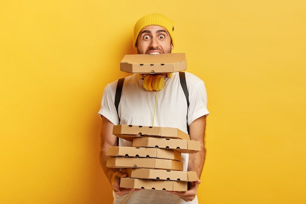 過負荷のピザ屋の肖像画は、多くの段ボールのパッケージを持っており、1つは口の中にあり、カジュアルな白いtシャツを着ています。