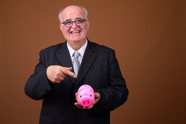 Портрет старшего бизнесмена с избыточным весом, держащего копилку