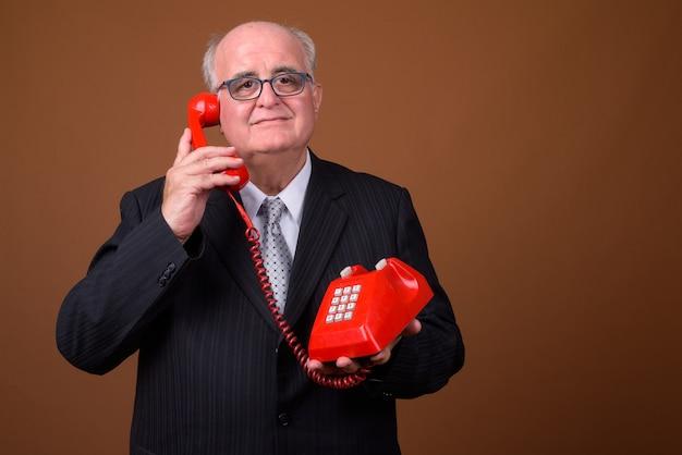 Портрет старшего бизнесмена с избыточным весом разговаривает по телефону