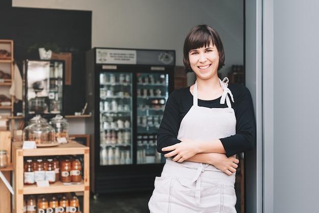 지속 가능한 소규모 지역 비즈니스 소유자의 초상화입니다. 가게 내부 배경에 서 있는 제로 폐기물 가게의 가게 주인. 플라스틱 무료 매장 입구를 환영하는 앞치마를 입은 웃는 젊은 여성