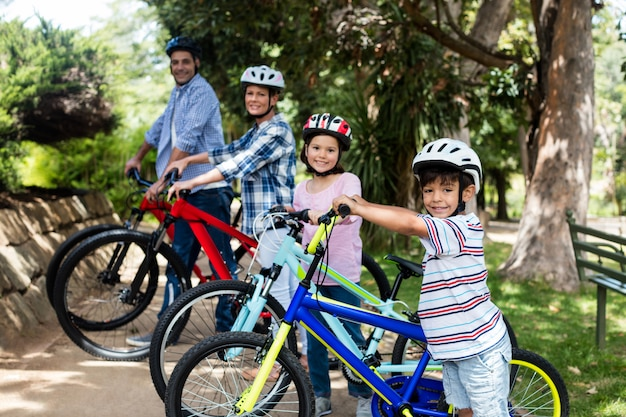 Портрет родителей и детей, стоящих с велосипедом в парке