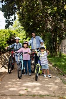 부모와 어린이 공원에서 자전거와 함께 서의 초상화