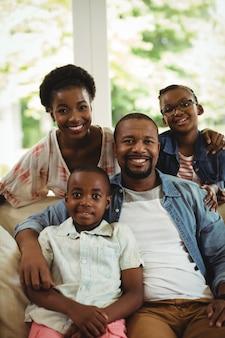 Портрет родителей и детей, сидя на диване в гостиной