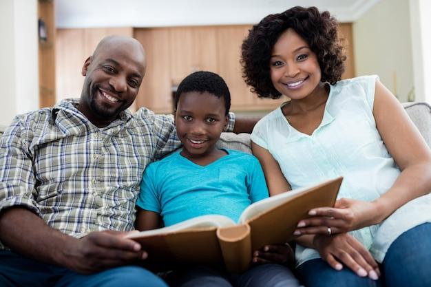 リビングルームでフォトアルバムを見て両親と息子の肖像画