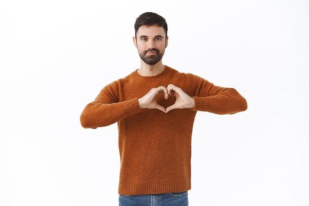 Портрет страстного красивого кавказского мужчины, показывающего знак сердца, романтического мужа, выражающего страсть и сочувствие, влюбленного в человека, стоящего на белой стене