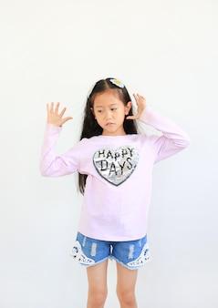 흰색 배경에 격리된 평화로운 아시아 어린 소녀 자세의 초상화.