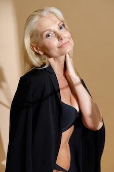 下着と上に笑みを浮かべて古典的な黒のジャケットで平和な成熟したブロンドの女性の肖像画