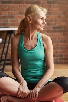 自宅でのトレーニングの後に床に座って微笑んで平和でスポーティーな成熟した女性の肖像画