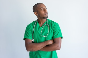 Portrait of pensive African American doctor standing with folded arms.