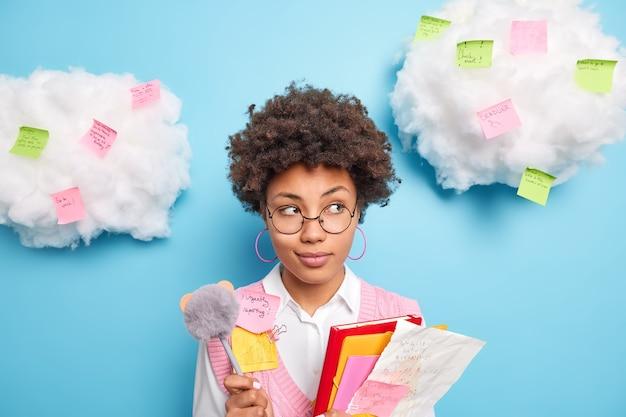 物思いにふけるアフリカ系アメリカ人の女子学生の肖像画は、紙のフォルダーを保持し、大学での講義中にペンでメモを取り、周りにステッカーを思い出させる雲に対する試験ポーズの資料を学びます