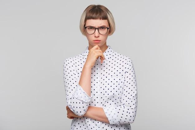 Портрет задумчивой привлекательной блондинки молодой женщины носит рубашку в горошек