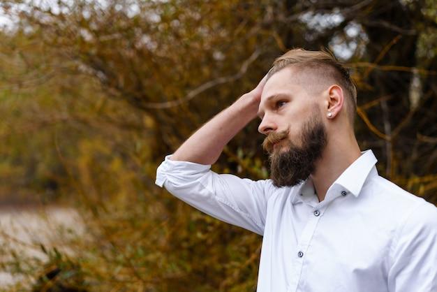 オクトブの秋の公園を見下ろす白いシャツの物思いにふけるひげを生やした魅力的な若い男の肖像...