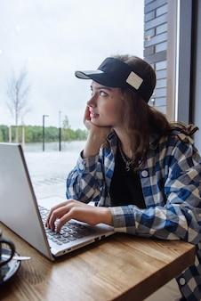 노트북과 함께 레스토랑에 앉아 잠겨있는 갈색 머리 여자의 초상화