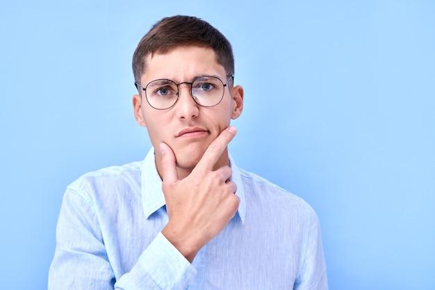 안경과 셔츠에 잠겨있는 남자의 초상화는 그의 턱을 잡고 생각하고, 결정을 내리고, 의심은 복사 공간이있는 파란색 스튜디오에서 격리
