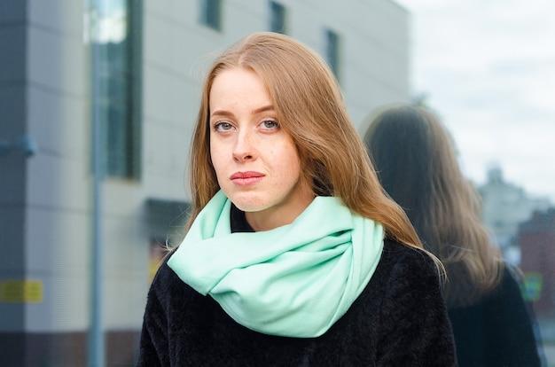 そばかすと青い目を屋外で物思いにふける赤毛の女性の肖像画