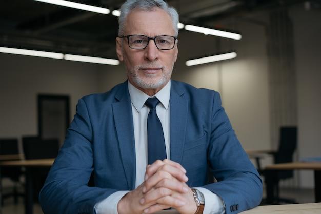 Портрет задумчивого старшего бизнесмена в костюме и очках, смотрящего в камеру, сидя в офисе