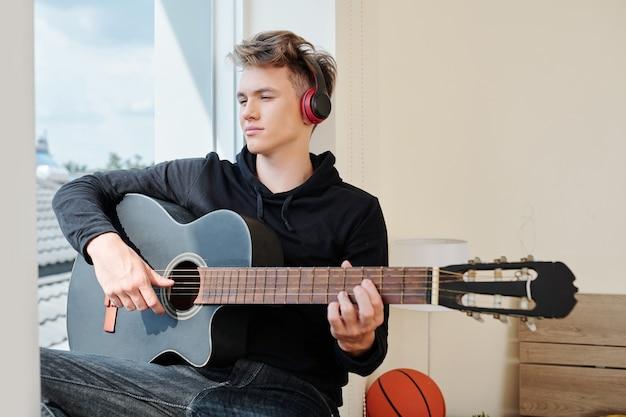 Портрет задумчивого подростка в наушниках, работающего над новой песней, сидя на подоконнике своей комнаты
