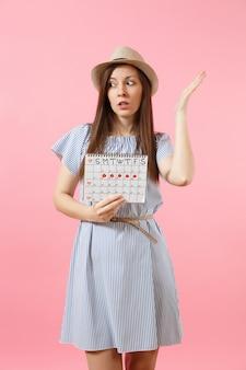 파란 드레스를 입은 수심에 찬 여성의 초상화, 밝은 분홍색 배경에 격리된 월경일을 확인하기 위한 기간 달력을 들고 있는 모자. 의료, 건강 관리, 부인과 개념입니다. 복사 공간