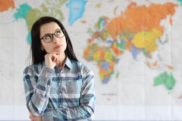 Портрет задумчивой женщины на фоне карты мира