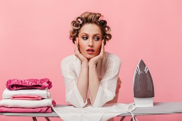 Портрет задумчивой женщины с бигуди, опираясь на гладильную доску на розовой стене