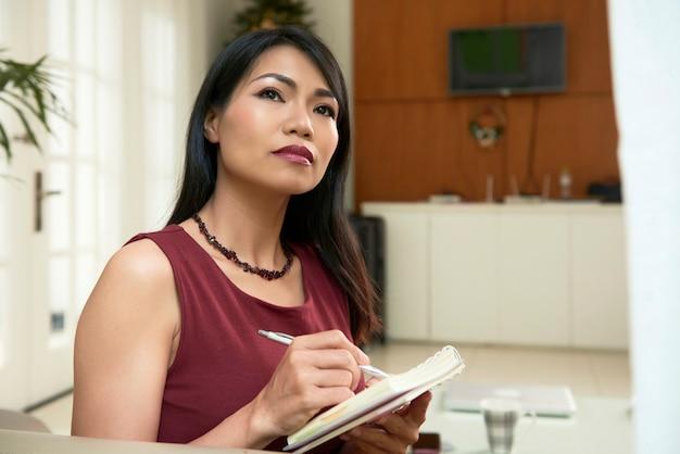 Портрет задумчивой молодой красивой женщины, заполняющей журнал, записывая свои мысли и идеи
