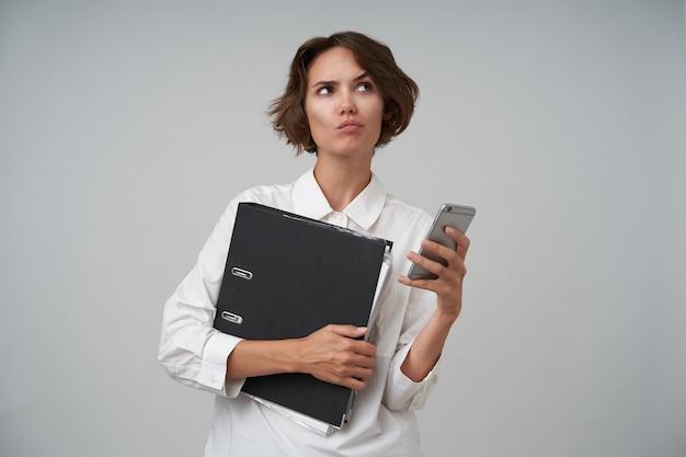 흰색 셔츠를 입고 잠겨있는 젊은 갈색 머리 여성의 초상화, 문서와 그녀의 스마트 폰으로 사무실에서 일하고, 신중하게보고 눈썹을 올리는, 서