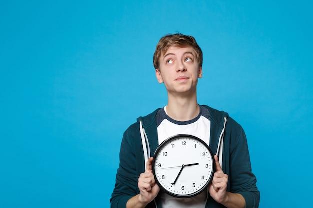 Портрет задумчивого молодого человека в повседневной одежде, глядя вверх, держа круглые часы, изолированные на синей стене. время уходит. люди искренние эмоции, концепция образа жизни.