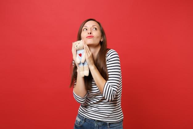 Портрет задумчивой молодой женщины в повседневной полосатой одежде, держащей плюшевую игрушку плюшевого мишку, смотрящую вверх