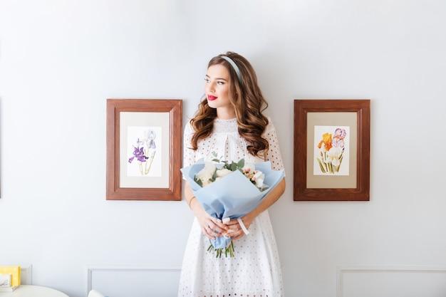 서서 꽃의 꽃다발을 들고 똥 드레스에 잠겨있는 젊은 여자의 초상화