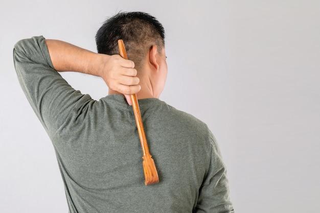Scratching wood stickを使用している人々の肖像画は、彼の後ろ側でscratchに固執します。