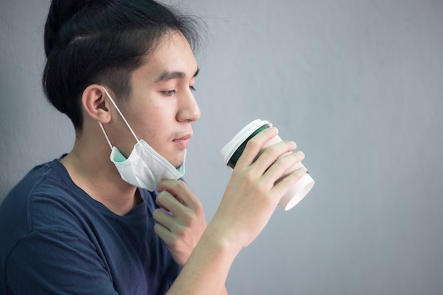 フェイスマスクを持つ人々の肖像画はコーヒーカップを保持します