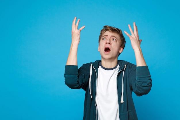 상승, 손을 확산, 파란색 벽에 고립 된 찾고 캐주얼 옷에 당황한 염증 된 젊은 남자의 초상화. 사람들은 성실한 감정, 라이프 스타일 개념.