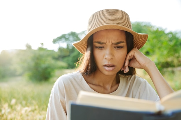 Портрет озадаченной женщины с пирсингом в губе и соломенной шляпе, читающей книгу, сидя на траве в зеленом парке