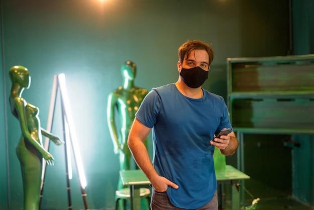 녹색 예술 스튜디오 룸 내부 코로나 바이러스 발생으로부터 보호하기 위해 마스크가있는 페르시아 남자의 초상화
