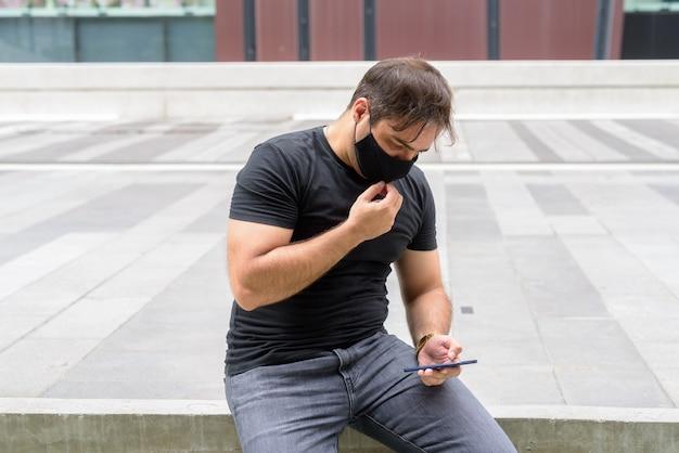 도시의 쇼핑몰에서 코로나 바이러스 발생으로부터 보호하기 위해 마스크가있는 페르시아 남자의 초상화