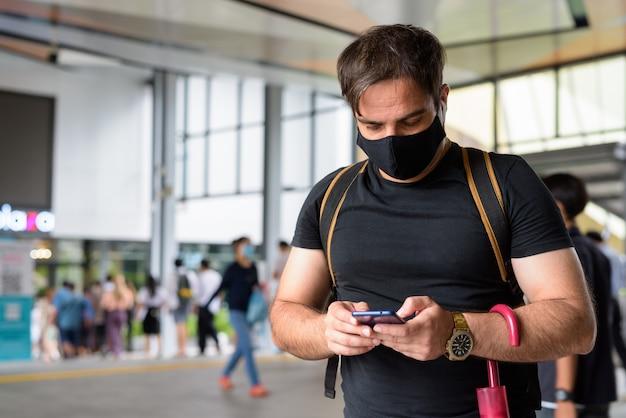 야외 도시의 쇼핑몰에서 코로나 바이러스 발생으로부터 보호하기 위해 마스크가있는 페르시아 관광 남자의 초상화