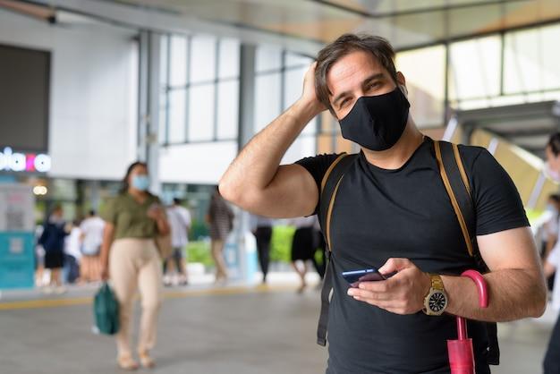 도시의 쇼핑몰에서 코로나 바이러스 발생으로부터 보호하기 위해 마스크가있는 페르시아 관광 남자의 초상화