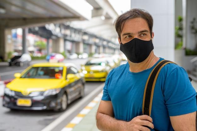 도시의 택시 정류장에서 코로나 바이러스 발생으로부터 보호하기 위해 마스크가있는 페르시아 관광 남자의 초상화