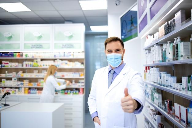 Портрет фармацевта в маске и белом халате показывает палец вверх в аптеке во время пандемии вируса короны.