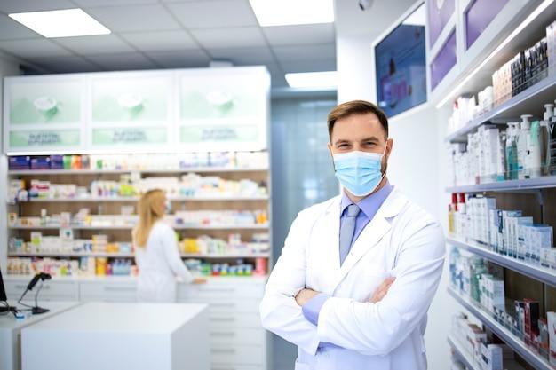 Портрет фармацевта в маске и белом халате, стоящего в аптеке во время пандемии вируса короны.