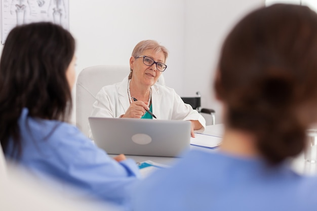회의실에서 책상에 앉아 의료 약물 치료를 설명하는 의사 수석 여성 의사의 초상화. 병원 팀워크로 의료 전문성을 분석하는 전문 의사