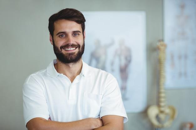 Портрет физиотерапевта, стоя со скрещенными руками