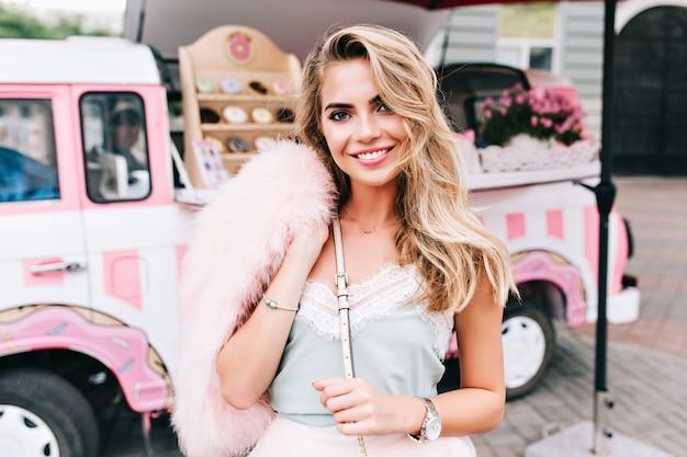 レトロなコーヒー車の背景に長いブロンドの髪を持つスタイルの女の子をピンで留めるの肖像画。彼女はカメラに微笑んでいます。